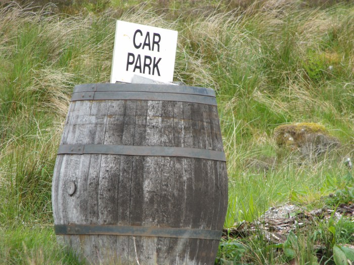 Black and white car park sign stuck into a barrel on grass