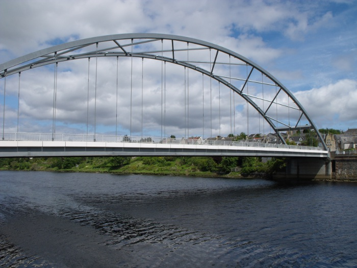 A view of Bonar Bridge in the daylight, blue sky with clouds in the background