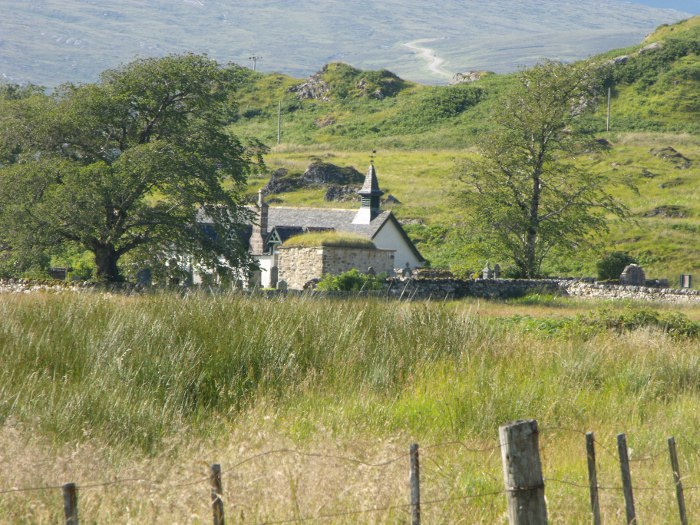 The Kirk in its natural setting, fence posts in the foreground and mountains in the background
