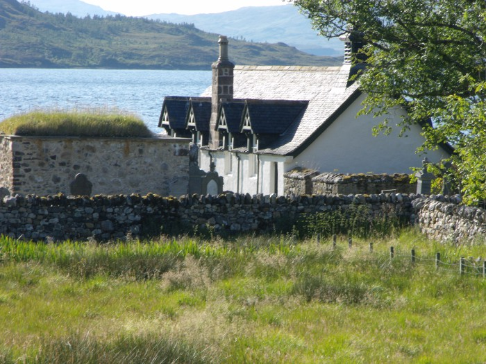 The turf-roofed MacLeods' tomb standing in front of the Kirk, with Loch Assynt behind
