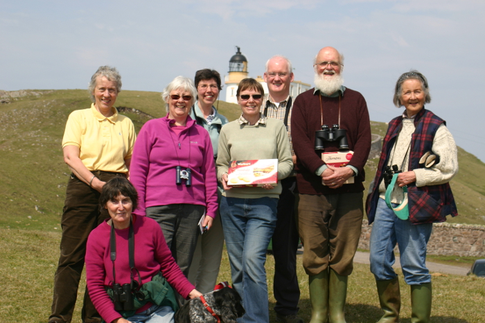 A happy group of birders with the lighthouse in the background