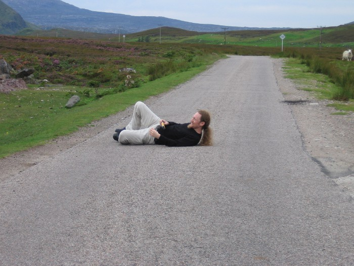 Bearded man lying in an empty road holding a camera
