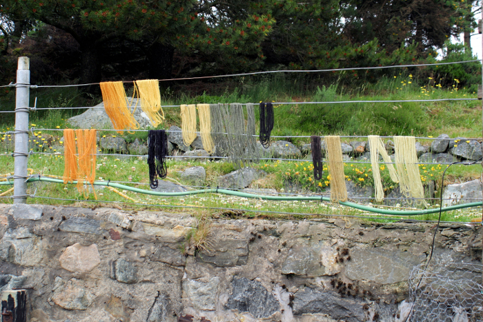 The yarns hanging on the fence to dry